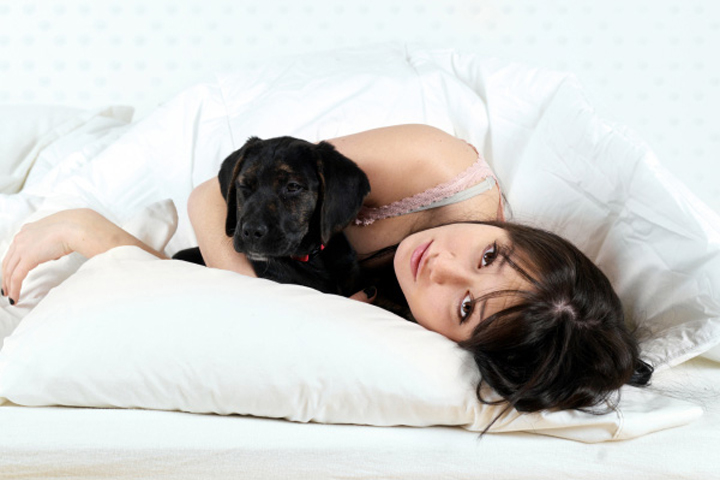 lady sleeping with a dog in bed